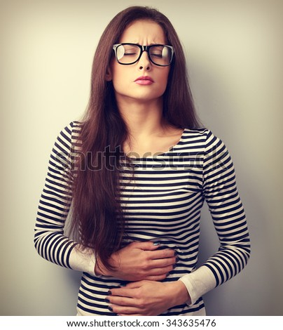 Beautiful stressed business woman in eyeglasses suffering from pain in stomach. Vintage closeup portrait