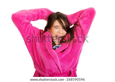 Beautiful stretching and yawning woman wearing pink bathrobe. - stock photo