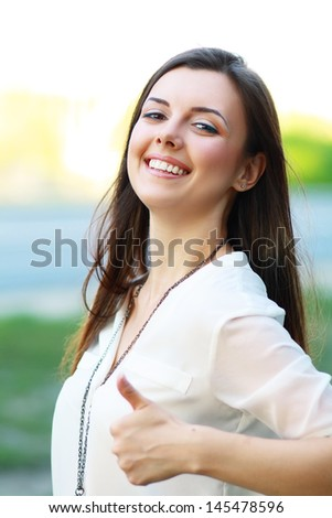 Beautiful student girl in white blouse lifts thumb upwards