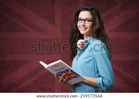 Beautiful student girl posing with an open book and smiling - stock photo