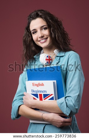 Beautiful student girl posing with books and smiling at camera - stock photo