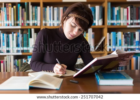 Beautiful student girl studying in college library. Writing notes from book at her notebook. Selective focus on face.  - stock photo