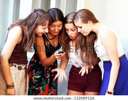 Beautiful student girls looking message on mobile phone - stock photo