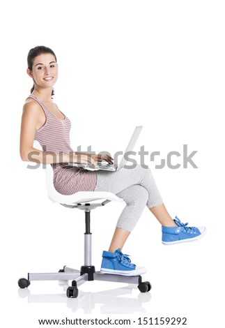 Beautiful student sitting in a chair with a laptop, isolated over a white background