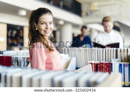 Beautiful student studying in library - stock photo