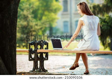 Beautiful student woman is using a laptop and sitting on a bench in the university campus. Smiling woman is working on a computer outdoors in the college park. Studying outdoors concept.  - stock photo