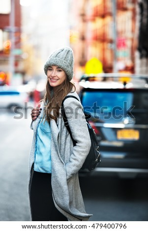 Beautiful student woman ready to get into her car parked on city street. Cute smiling woman wearing autumn casual street style outfit and backpack walking on city street.
