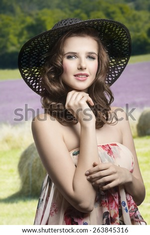 Beautiful, stunning brunette woman with curly hairstyle wearing summer hat and delicate dress with floral print. - stock photo