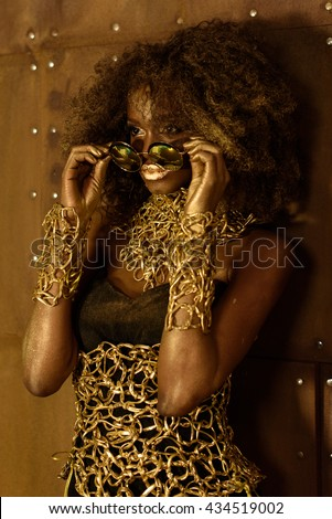 Beautiful stunning portrait of an african american young woman with afro hair. Girl wearing fashionable gold sunglasses