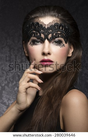 Beautiful, stunning, romantic woman with long brown hair, beautiful, dark make up with little pattern, transparent, black mask on her face. She is looking at camera. - stock photo