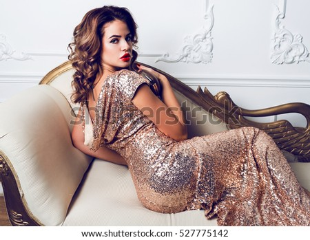 Beautiful stunning young woman  in amazing glitter sequins dress  sitting on luxury armchair , holding  trendy evening hand bag. Bright red full lips, hollywood make up.