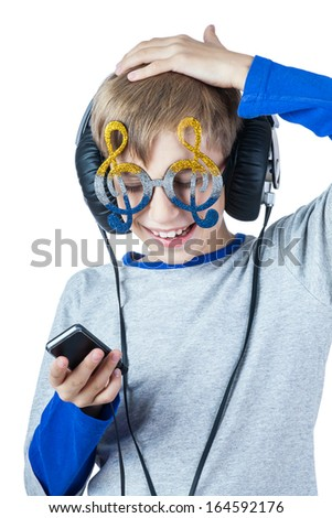 Beautiful stylish blond child wearing big professional headphones and funny glasses laughing  (music concept) - stock photo