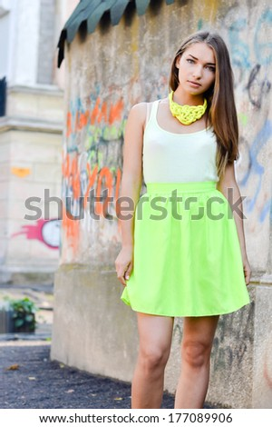 Beautiful stylish fashion woman at graffiti wall in city with flying hair on summer outdoors background  - stock photo