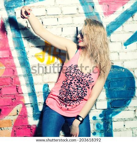 Beautiful stylish fashionable blonde makes Selfie near graffiti wall - stock photo