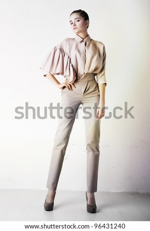 Beautiful stylish girl in fashion trousers posing isolated on white wall - stock photo