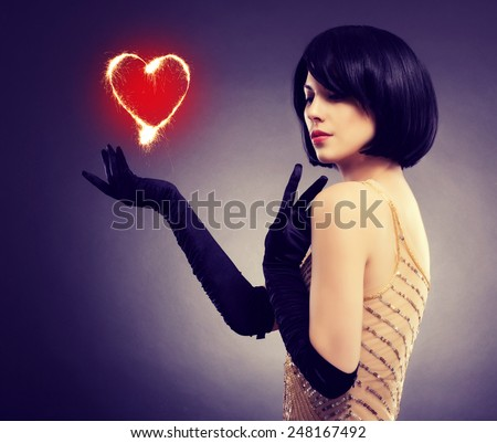 Beautiful stylish girl with a flaming heart in his hand. The concept of Valentine's Day.