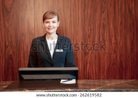 Beautiful stylish hotel receptionist standing behind the service desk in a hotel lobby looking at a guest with a friendly smile - stock photo