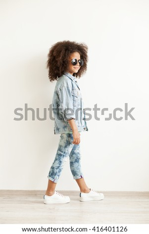 Beautiful stylish little girl in jean clothes - stock photo
