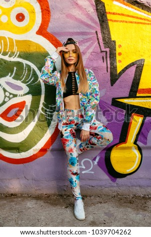Beautiful stylish model in sunglasses standing on background of wall with colorful graffiti. Dressed in fashionable suit, tank top and cap. Outdoors.