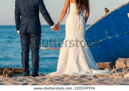 Beautiful stylish newlyweds sitting next to a boat on the beach. Gentle bride and handsome groom by the sea. - stock photo