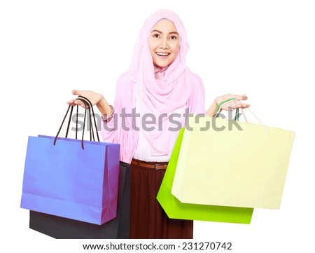 Beautiful stylish woman holding shopping bags in both hands, isolated on white background - stock photo