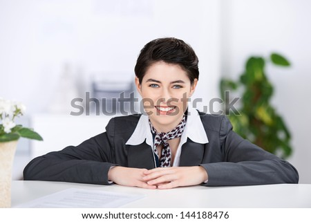 Beautiful stylish young female receptionist with a welcoming smile leaning her arms on the top of a counter as she waits to greet clients - stock photo