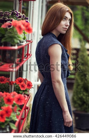 Beautiful stylish young girl dressed in casual clothes (dress and sneakers) walks through the streets of the city after the rain. the concept of fashion wear for women