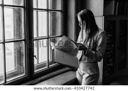 Beautiful stylish young  girl reading a book near the vintage  window in library. Black and white photo - stock photo