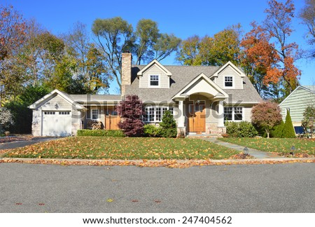 Beautiful suburban cape cod style home autumn clear blue sky day residential neighborhood USA - stock photo