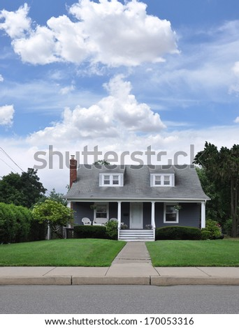 Beautiful Suburban Cape Cod Style Home Landscaped Front yard Lawn Residential Neighborhood Blue Sky Clouds USA - stock photo