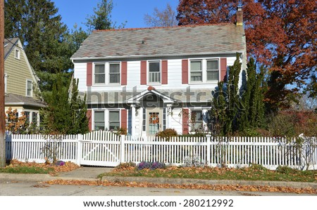 Beautiful Suburban Colonial Home with white picket fence autumn clear blue sky day residential neighborhood USA - stock photo