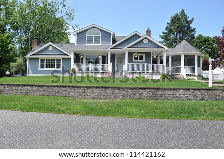 Beautiful Suburban Craftsman Cottage style Home with Landscaped Front Yard Lawn and brick wall - stock photo