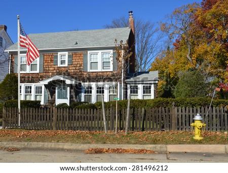 Beautiful Suburban Georgian style home wood shingles fence sunny clear blue sky autumn day residential neighborhood USA - stock photo