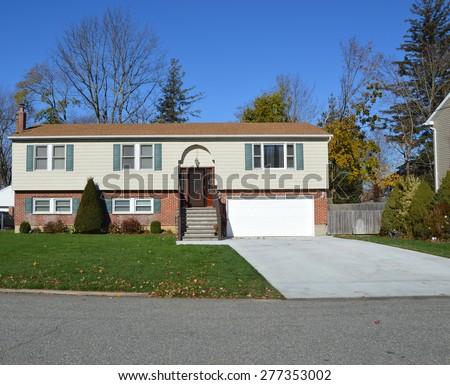 Beautiful Suburban High Ranch Brownstone Brick Siding Home Residential Neighborhood Clear blue sky USA - stock photo