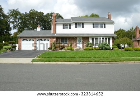 Beautiful Suburban High Ranch Two Car Garage Home Overcast Sunny Day Front yard Residential Neighborhood USA - stock photo