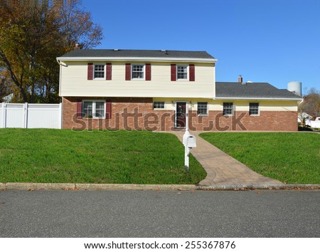 Beautiful Suburban McMansion Brick and Siding Mailbox curbside sunny clear blue sky residential neighborhood USA