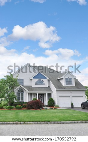 Beautiful Suburban McMansion style Home Landscaped Front yard Lawn Cobblestone curb Residential Neighborhood USA Blue Sky Clouds - stock photo