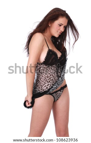 Beautiful sultry sexy young brunette woman wearing black and white transparent nightie negligee bra and pants and high heels posing for camera with fan blowing wind through her hair while she dances - stock photo