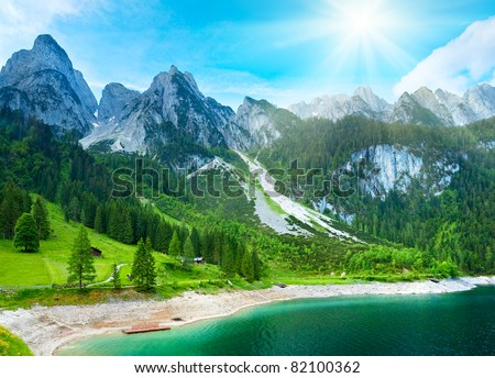 Beautiful summer Alpine mountain  lake view and sunshine in sky - stock photo