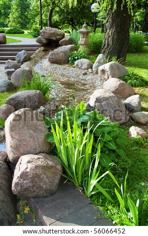 Beautiful summer garden with plants and stones - stock photo