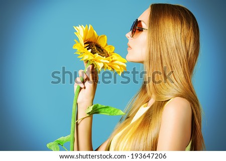 Beautiful summer girl in brigt yellow dress and sunglasses stands with a sunflower. - stock photo