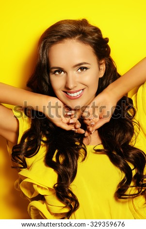 Beautiful summer girl in yellow dress smiling at camera, over yellow background. Beauty, fashion. Teeth care. - stock photo