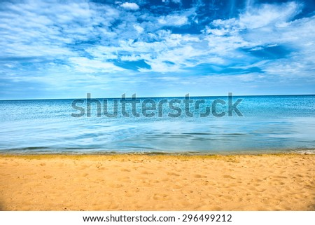 Beautiful summer sea abstract background. Golden sand beach with blue ocean and cloudscape and sunset - stock photo