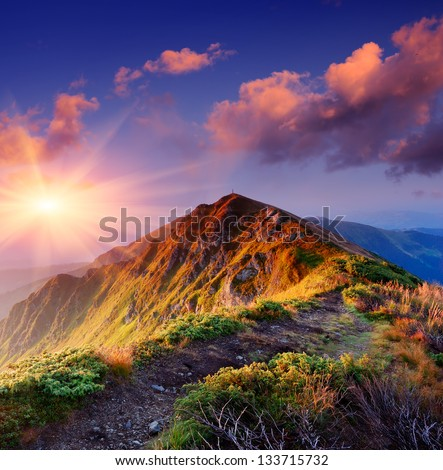 Beautiful summer sunrise in mountains. Path along the ridge leading to summit - stock photo