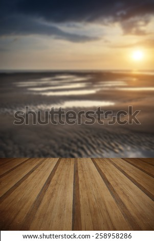 Beautiful Summer sunset over golden beach landscape with wooden planks floor - stock photo