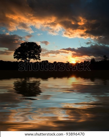 Beautiful Summer sunset silhouette reflected in still waters of lake - stock photo