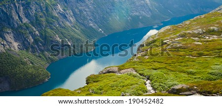Beautiful summer vibrant view on Norwegian fjord with a house, forest, rocks, blue sky and reflection. Norway Mountain Vibrant Landscape Trolltunga Odda Fjord Norge Hiking Trail  - stock photo