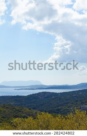 Beautiful summer view on the sea beach and mountain where is paved road and skyline with clouds and greenery trees from Italian Sardinia the best view on the island bay area from traveling vacation
