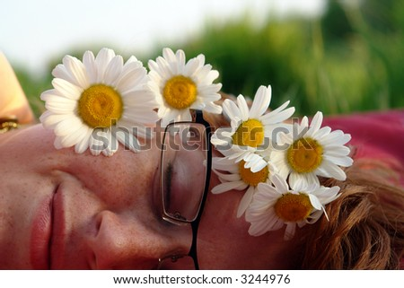 Beautiful summer woman lying in the grass with a daisy in her hair