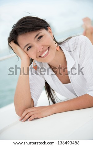 Beautiful summer woman lying on a boat enjoying her holidays
